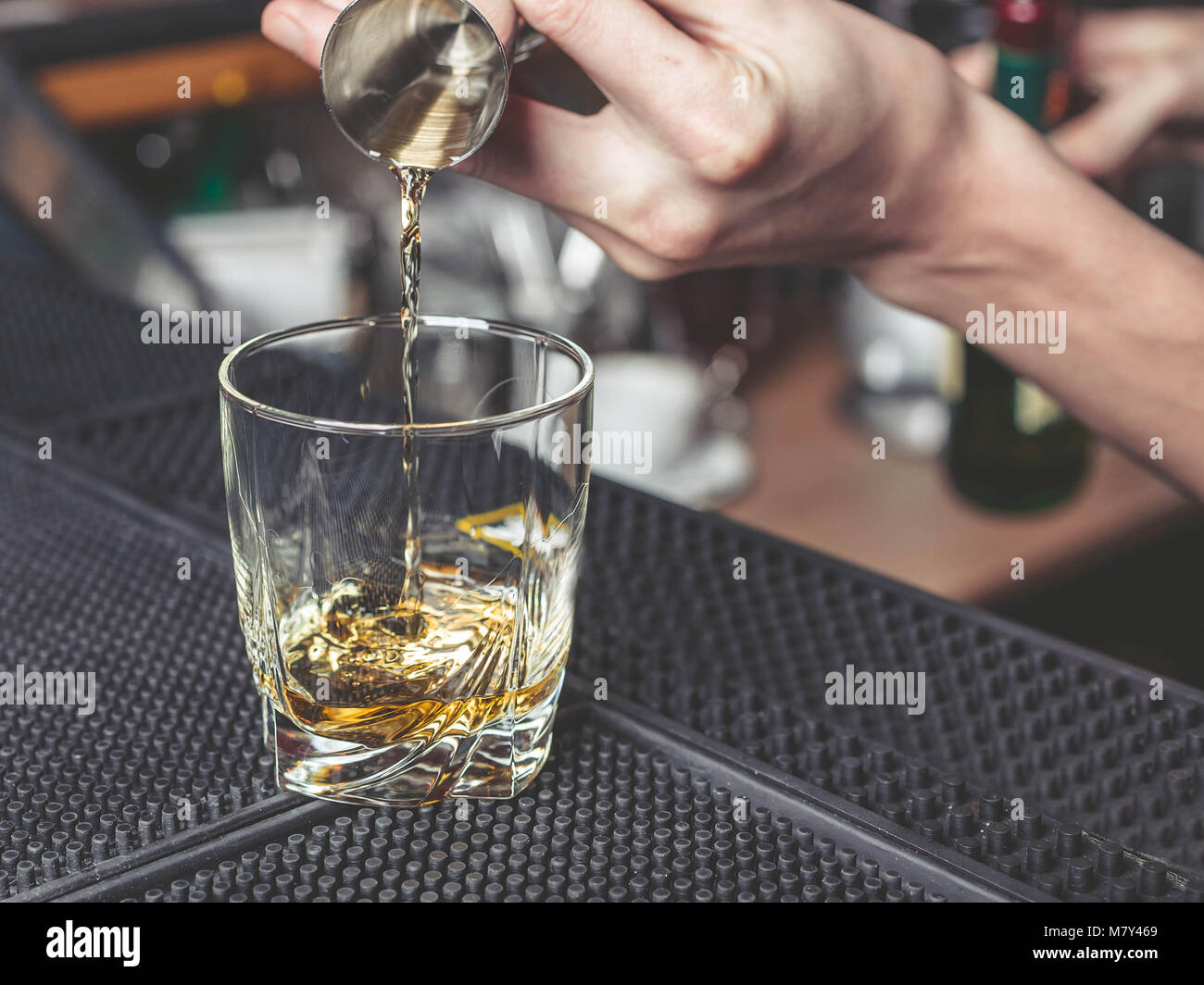 The barman pours whisky in a glass - Stock Image