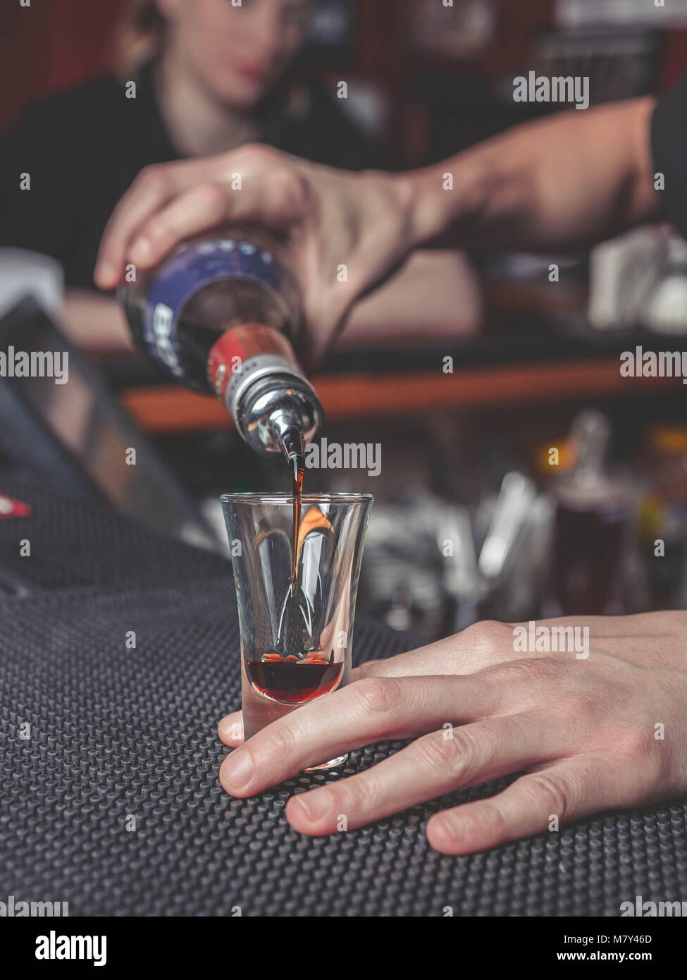 The barman pours liquor into a glass on the bar counter - Stock Image