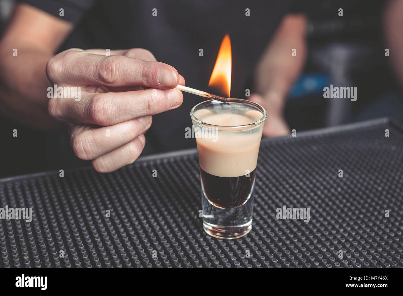 Barman flaming cocktail B-52 on the bar - Stock Image