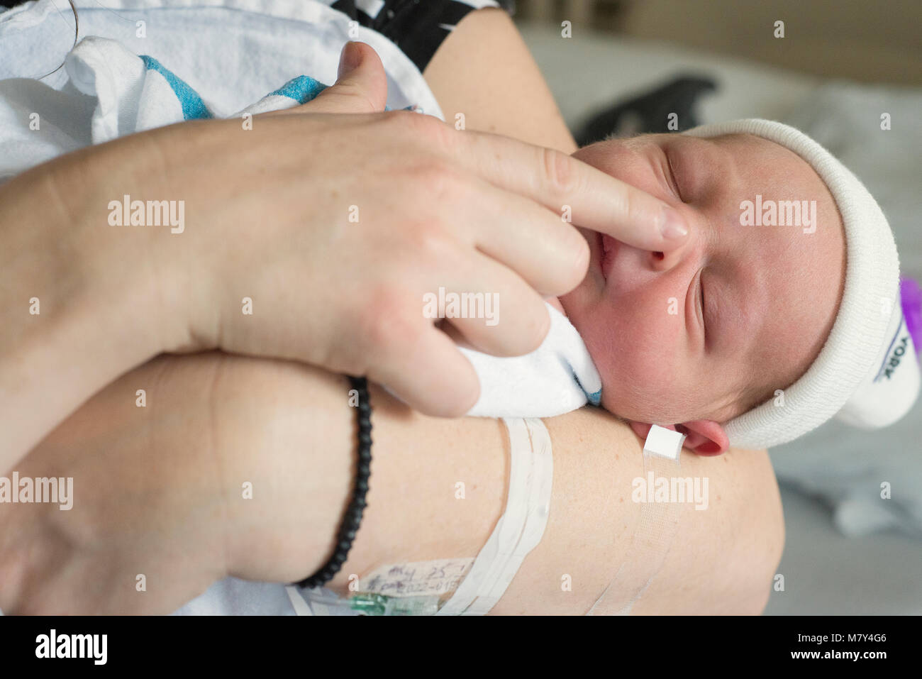A newborn baby being held in the hospital by it's mother the day it's born. - Stock Image