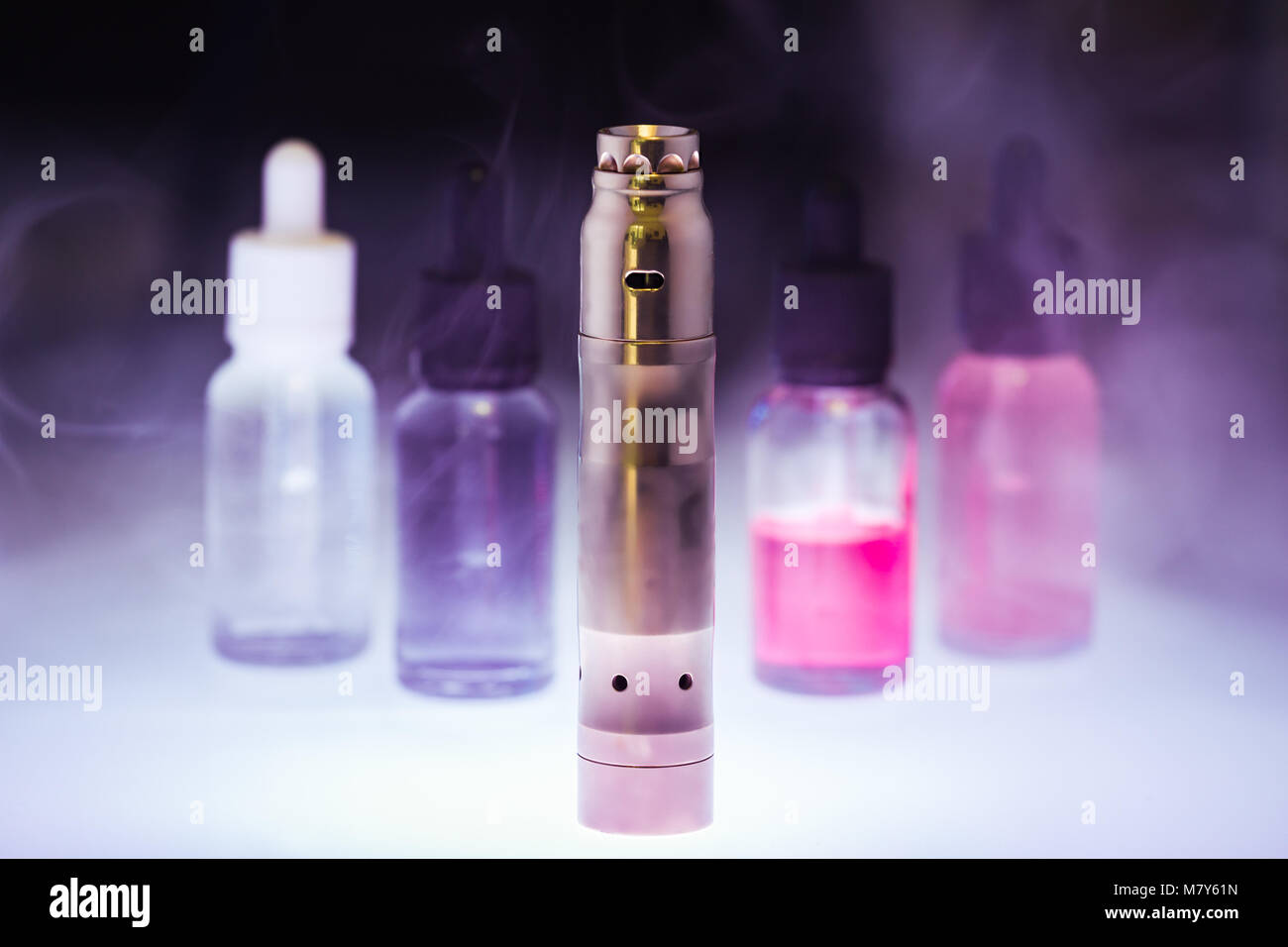 E-cigarette with four e-liquid in the white smoke on a dark background. E-juice from vape. Alternative to smoking - Stock Image