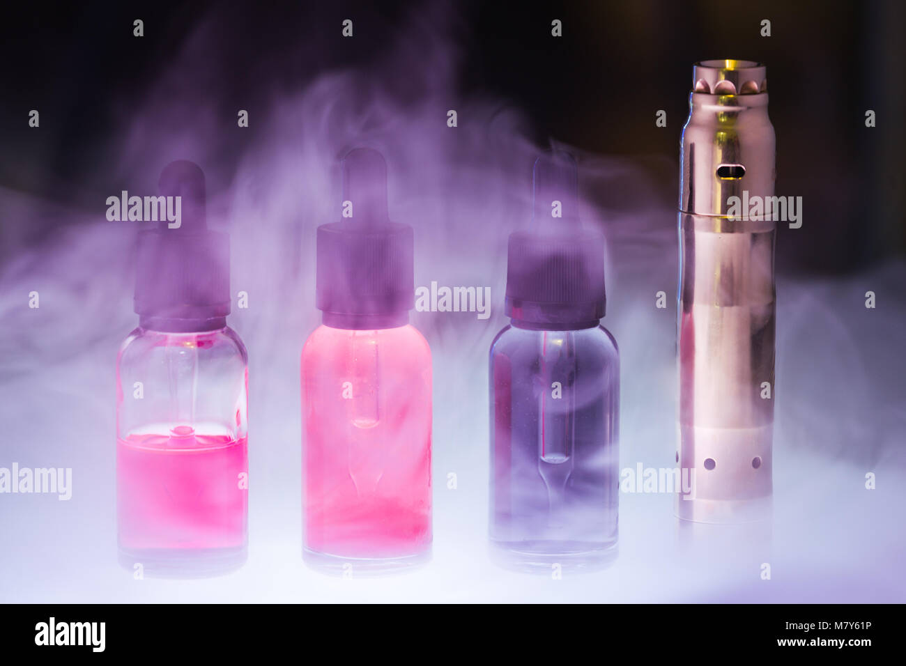 E cig with three e-liquid in the white smoke on a dark background. E-juice from vape. Alternative to smoking - Stock Image