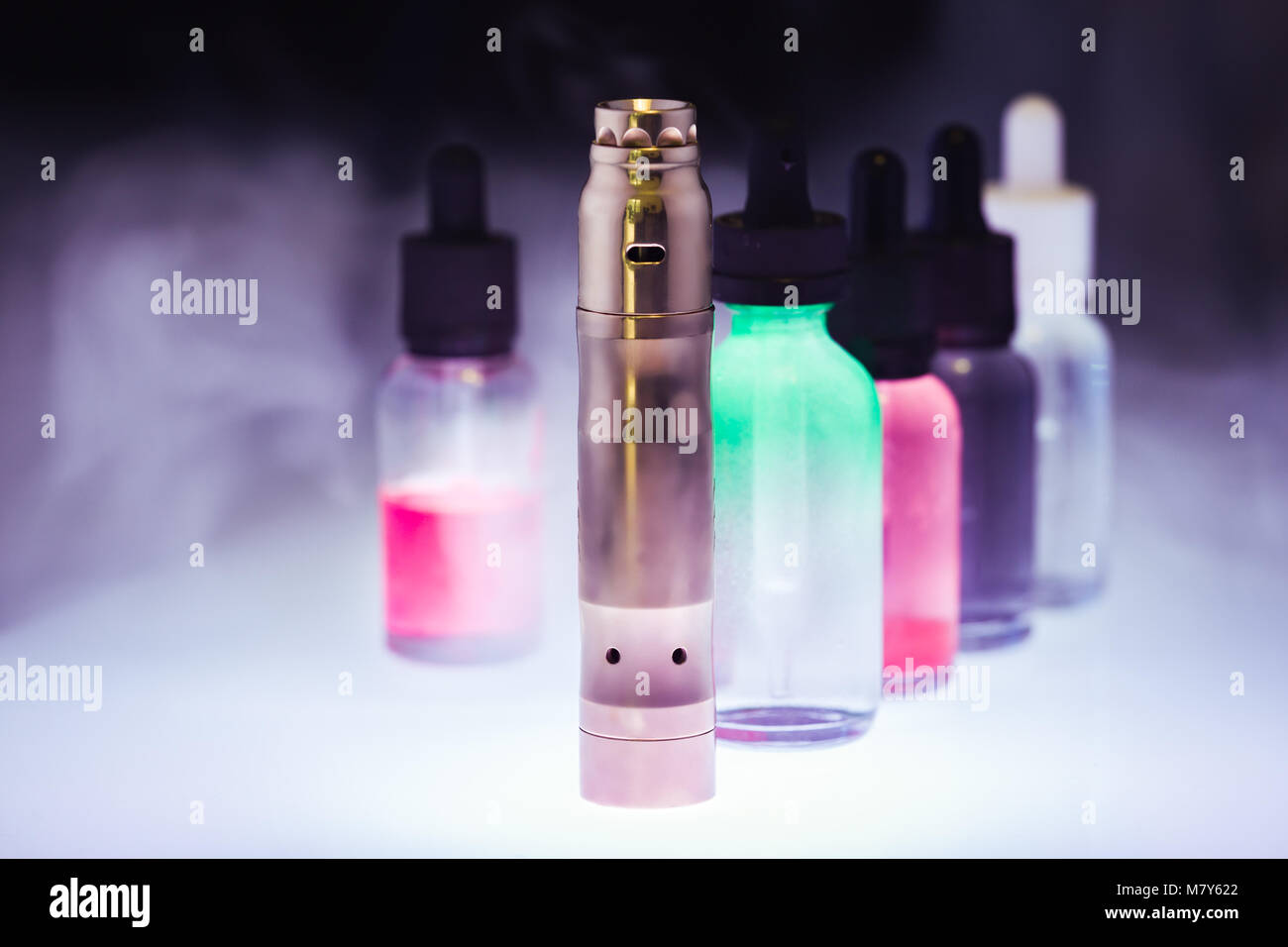 Electronic cigarette  with five e-liquid in the white smoke on a dark background. E-juice from vape. Alternative - Stock Image