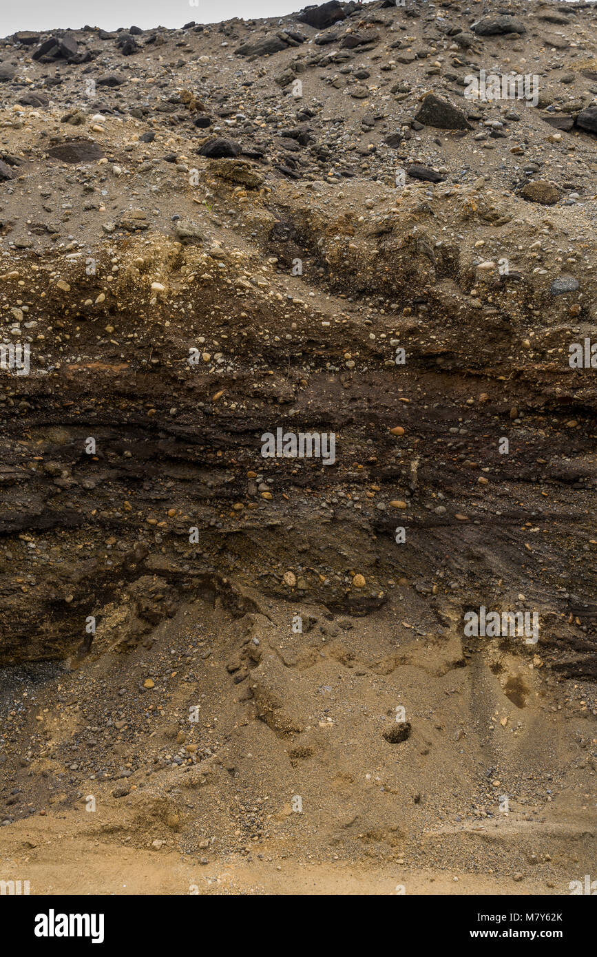 Multiple layers of earth showing deposits of ash from eruptions and volcanic activity, South Coast, Iceland - Stock Image