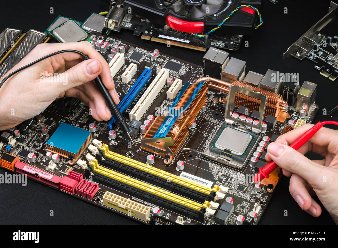 Diagnostics of the old motherboard with a voltmeter on a black table. Workplace repairman with special tools and - Stock Image