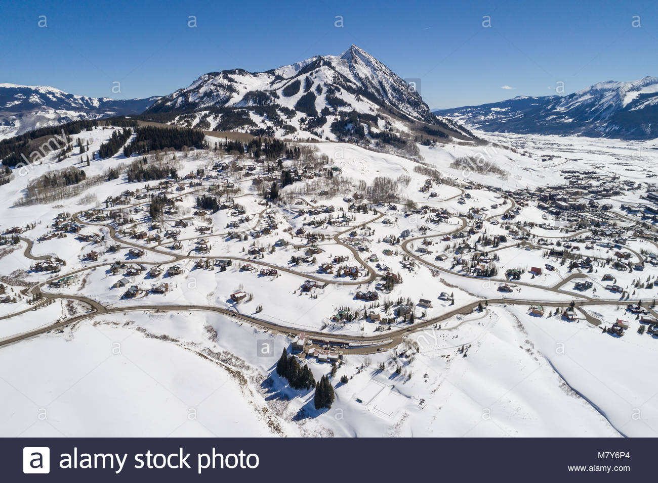 Aerial photograph of the snow-covered town of Mount Crested Butte, Colorado and Crested Butte Mountain on a winter - Stock Image