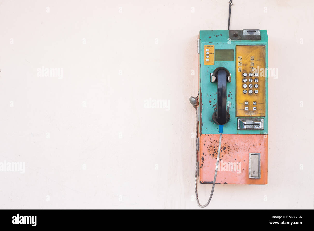 Old public phone using coin or card setting on the wall. With empty space for text - Stock Image