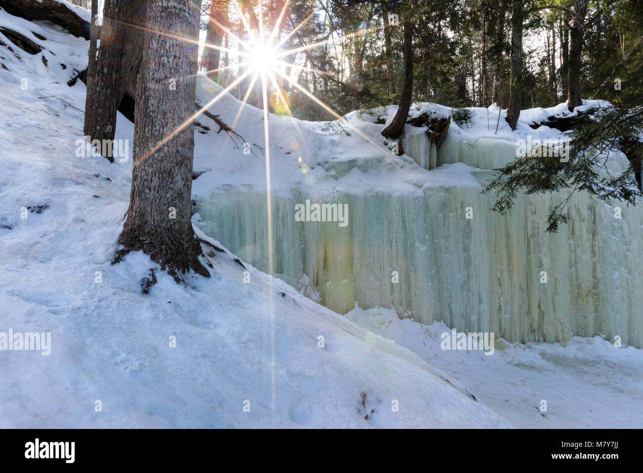 Eben Ice Caves in Michigan's Upper Peninsula spill over a rock ledge, like a waterfall, creating patterned ice - Stock Image