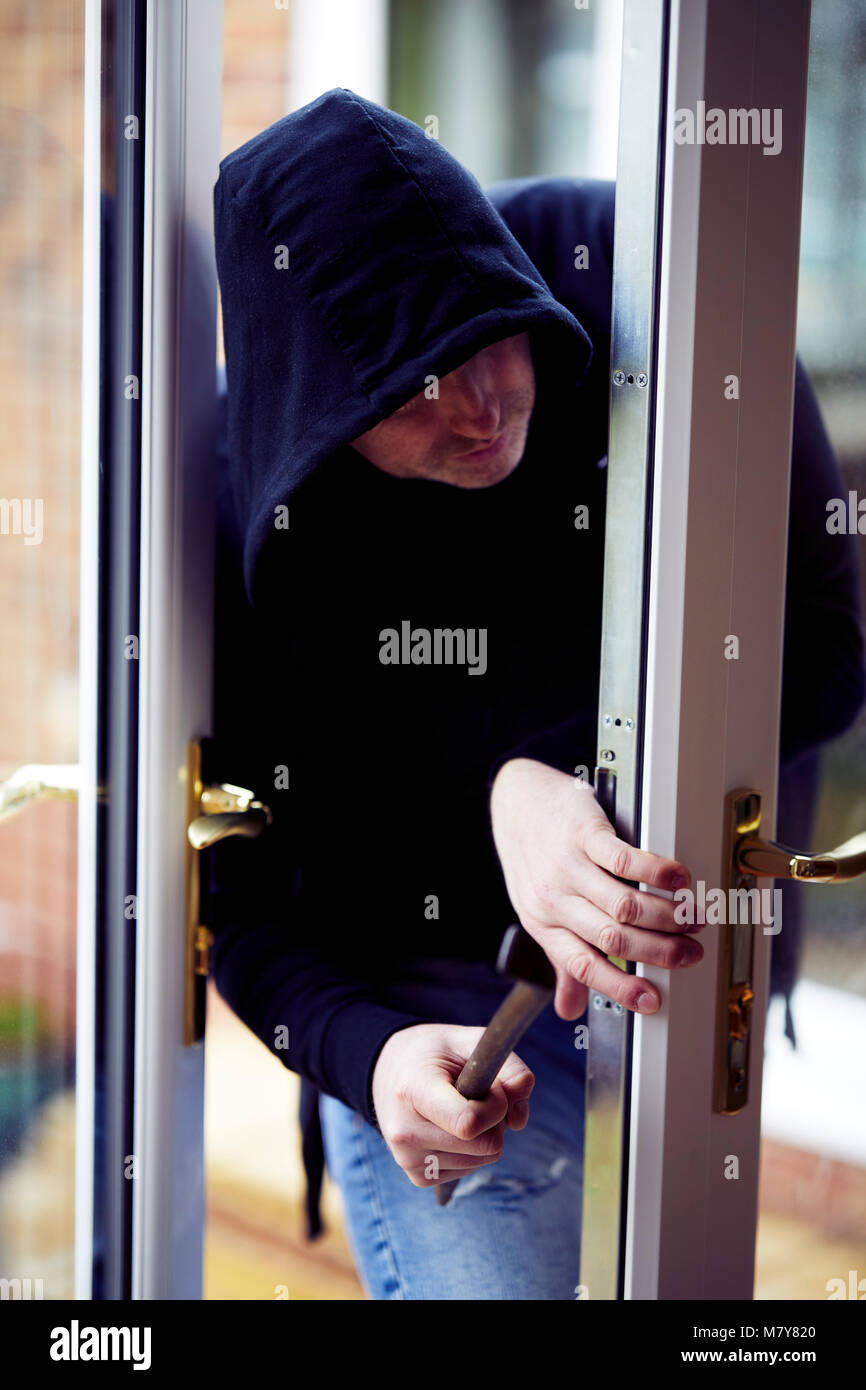 Person breaking into property - Stock Image