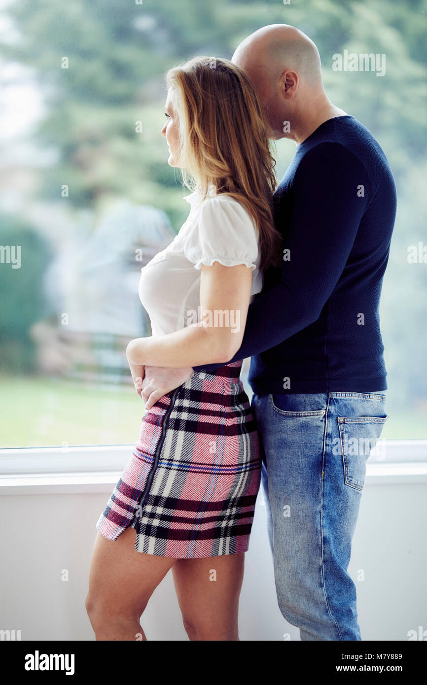 Couple stood looking out of window - Stock Image