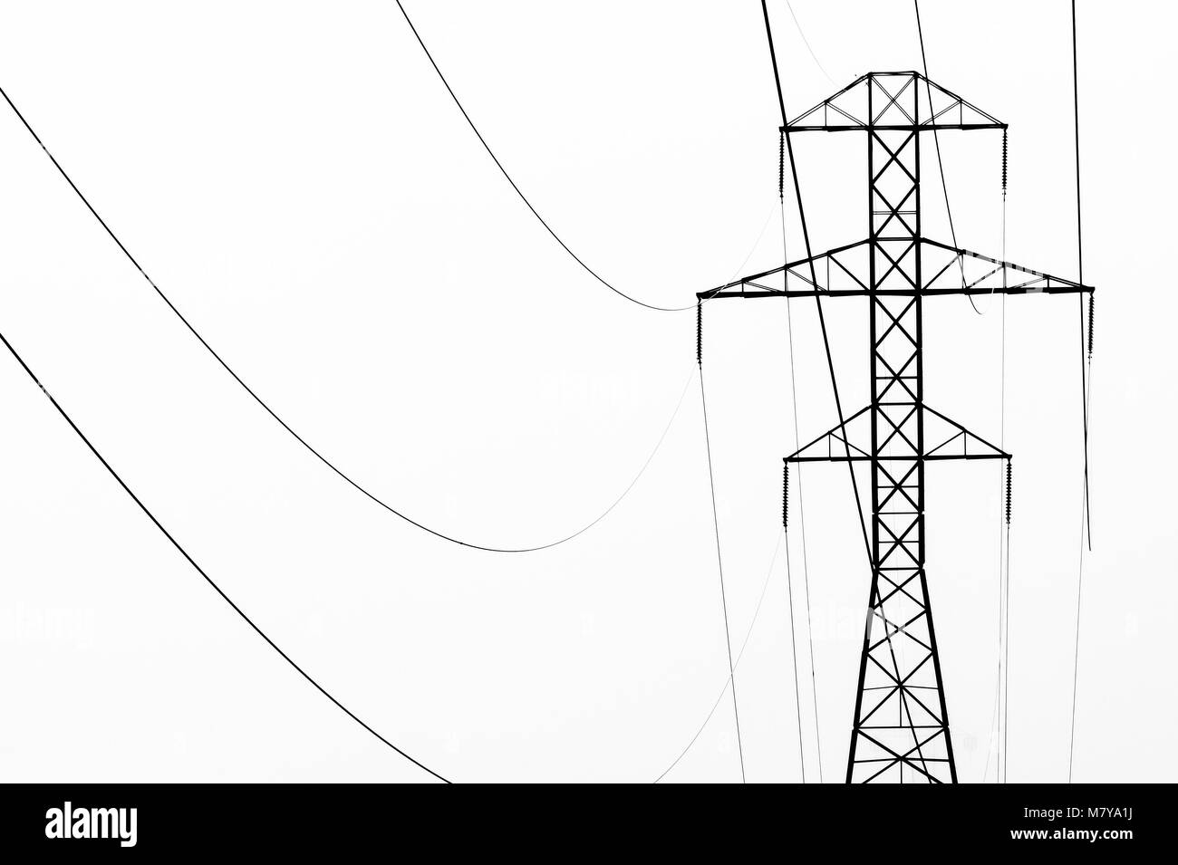 High key black and white abstract of powerline towers and fog. - Stock Image