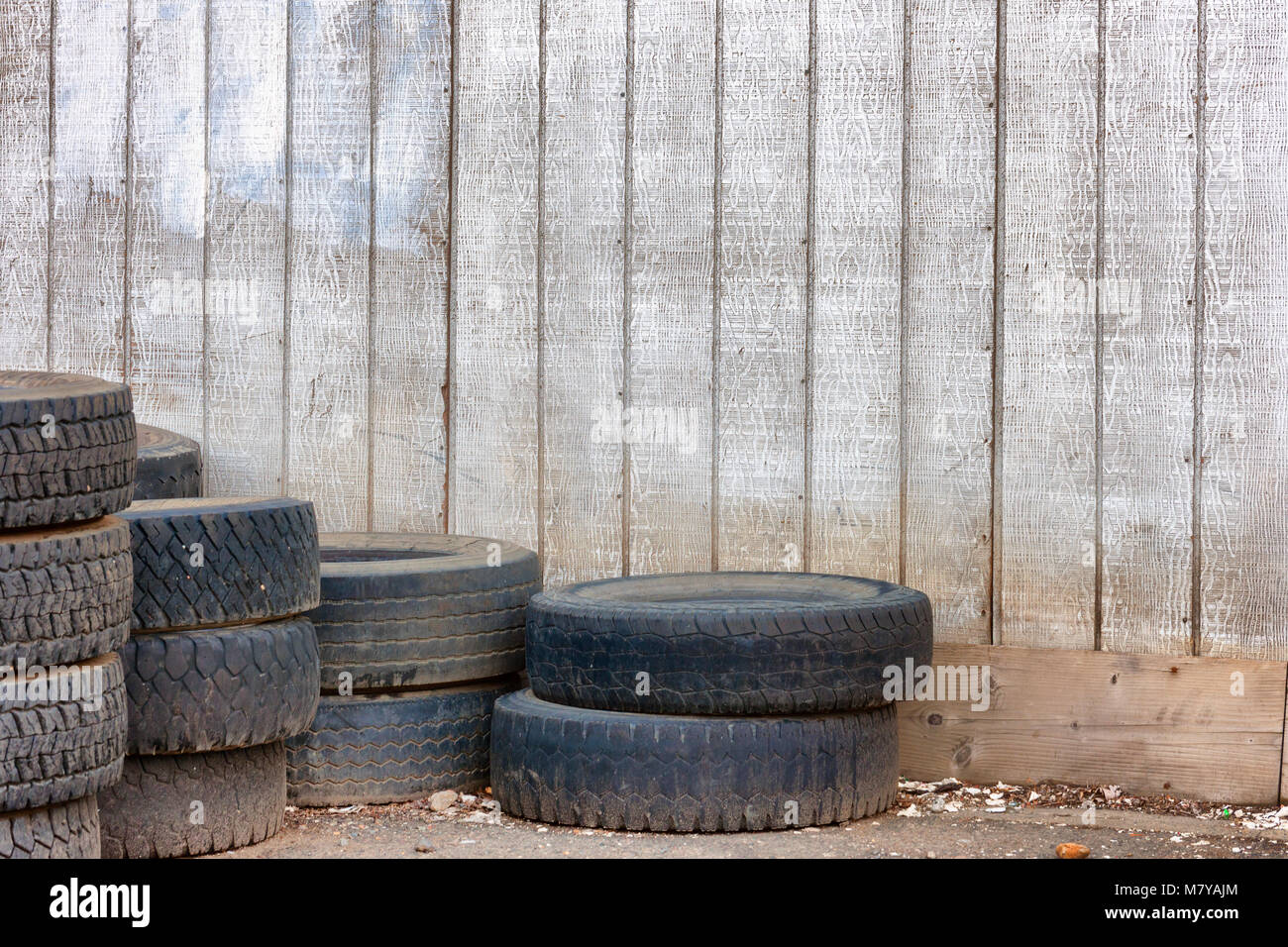 Junk tires stacked and left outside an old building. - Stock Image