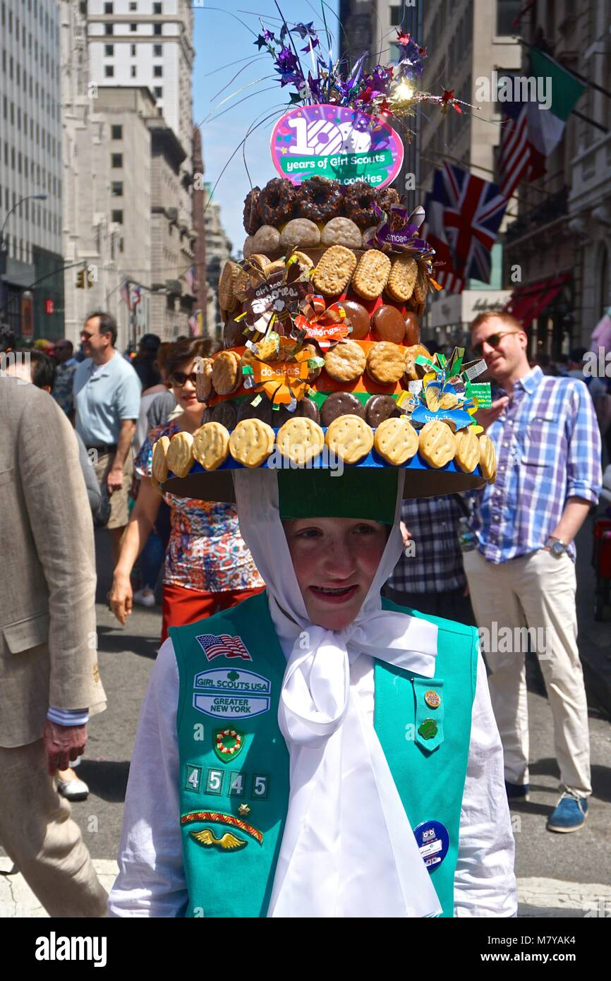Girl in a Girl Scouts uniform with a Girl Scout cookie bonnet at the Fifth Avenue Easter Parade in New York City. - Stock Image