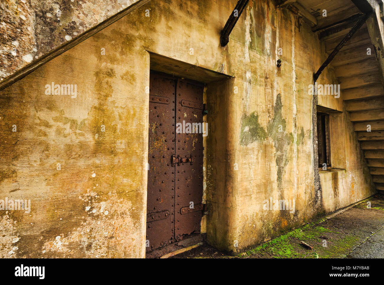 Exterior wall of an old abandoned bunker with steel door. Stock Photo