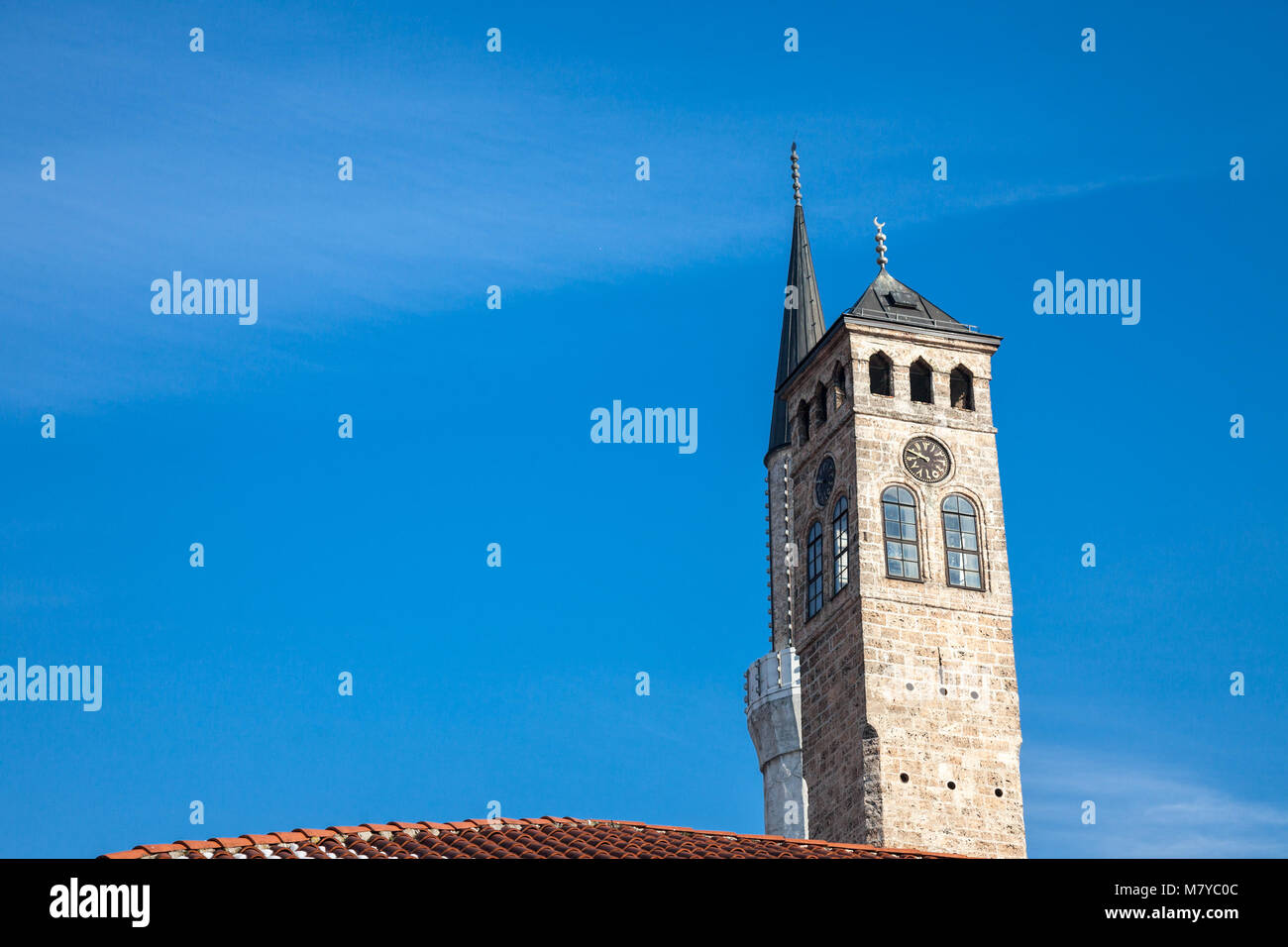 Minaret of the Gazi Husrev begova Mosque next to the clocktower of Sarajevo bazaar, in Bosnia and Herzegovina   Stock Photo