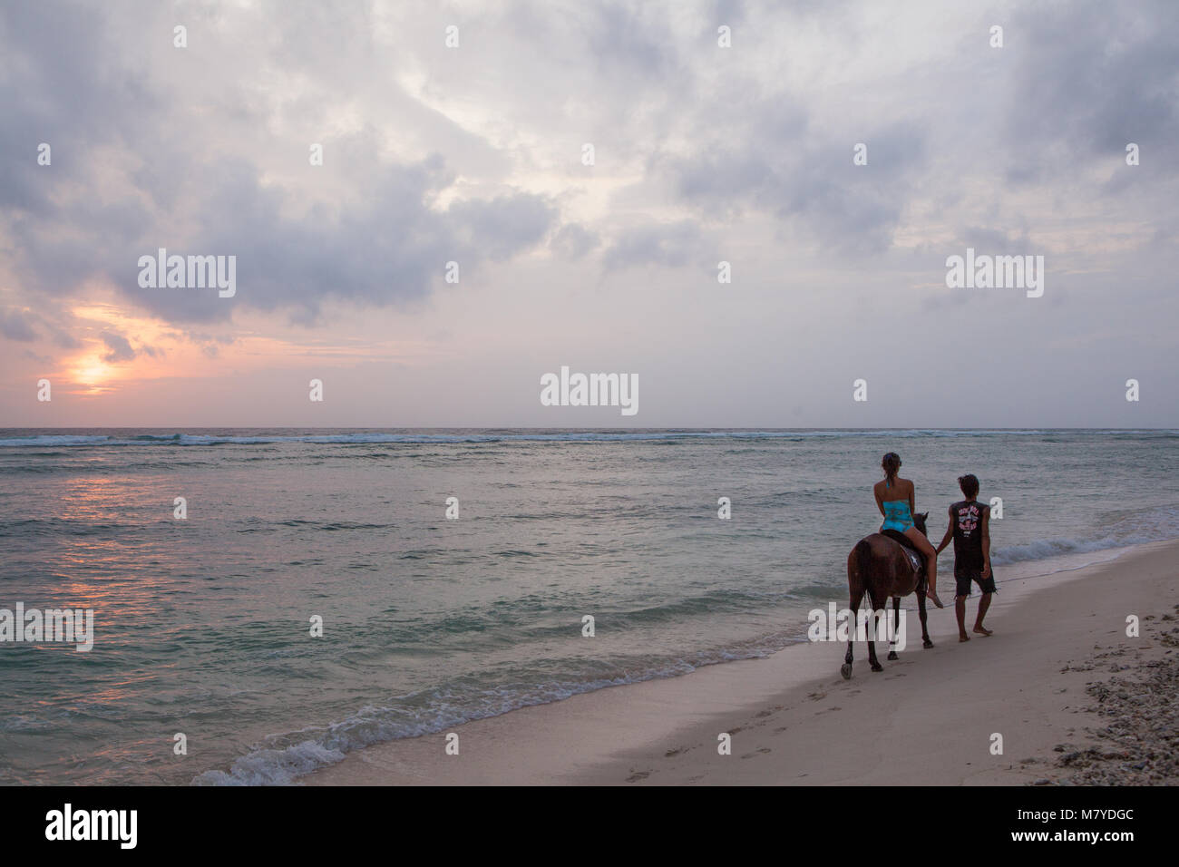 Girl horse riding on a deserted beach in Gili Trawangan, Indonesia, accompanied by a local guide walking on her - Stock Image