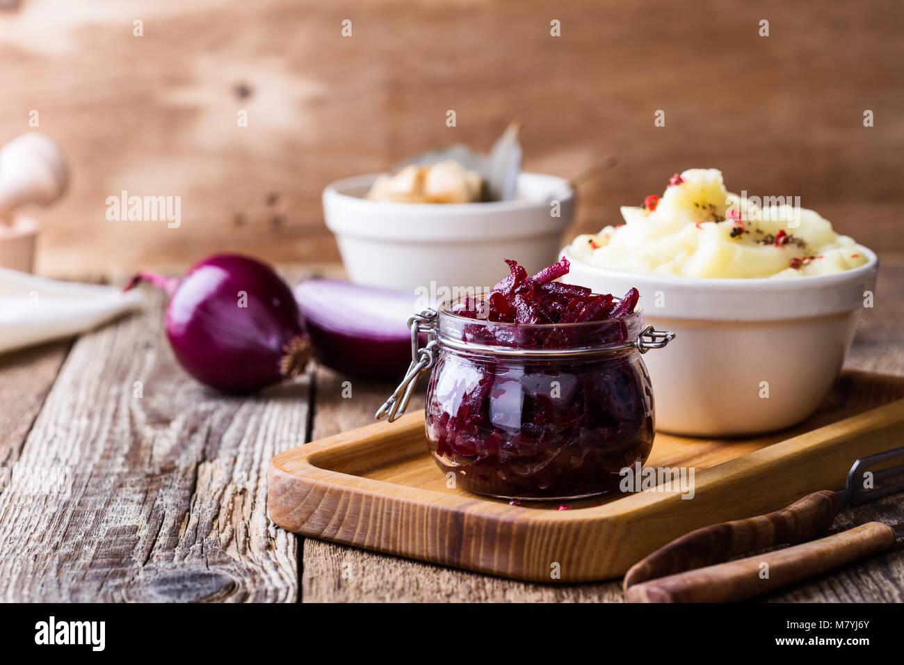 Healthy vegetarian meal. Mashed potatoes and homemade pickled mushrooms and beetroot salad on rustic wooden table - Stock Image
