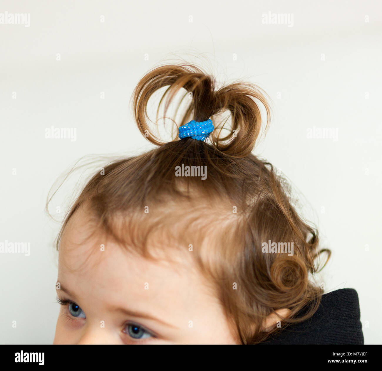 Hair hairstyle shaped fountain or onion of a toddler baby girl. - Stock Image