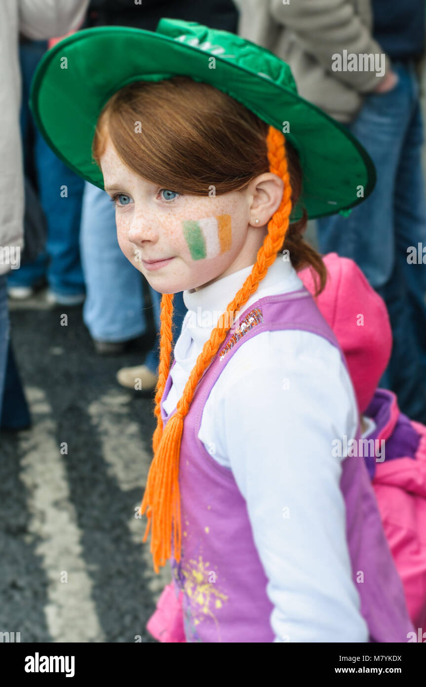 A girl in a hat with her  face painted in the colours of the Irish flag is pictured during St Patrick's Day - Stock Image