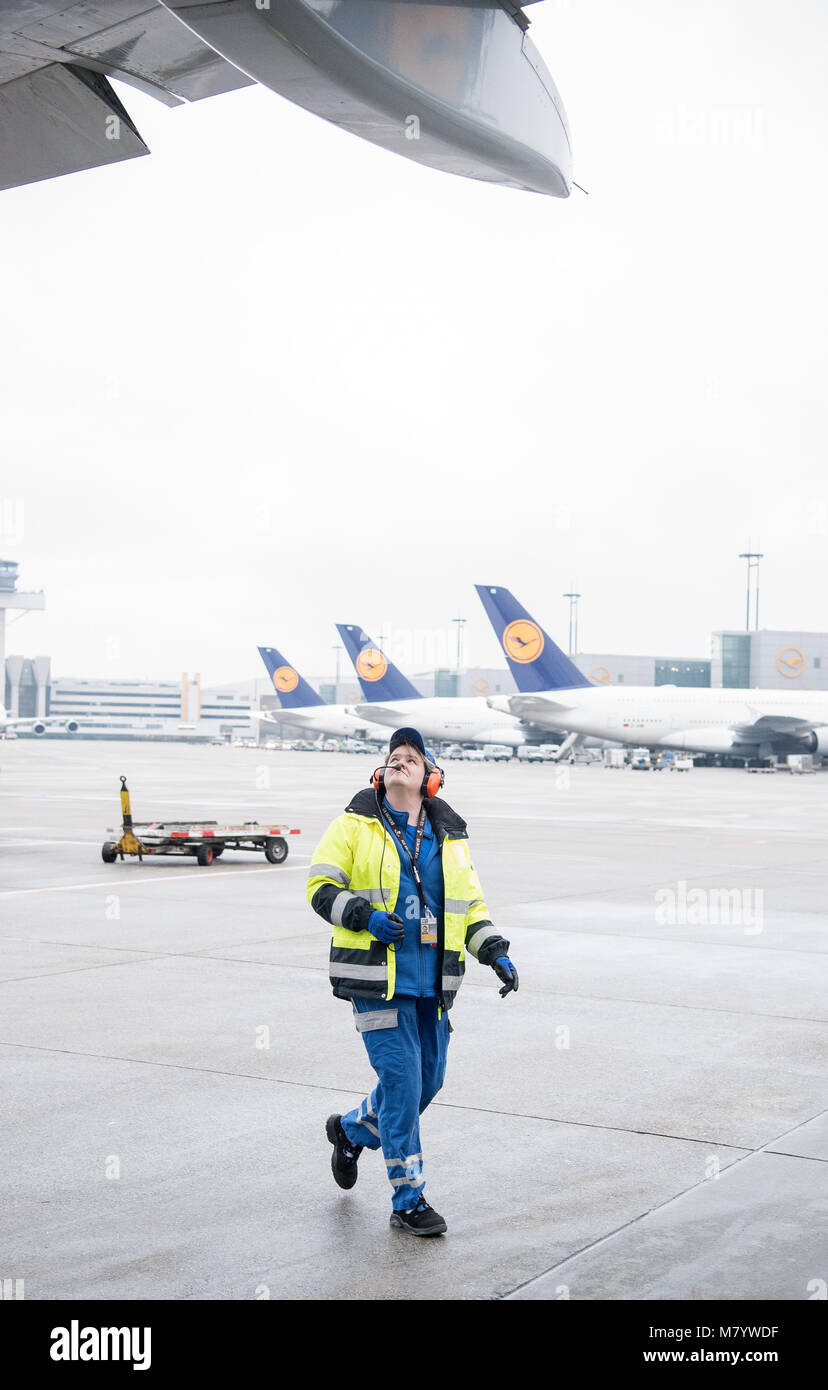 08 March 2018, Germany, Frankfurt: Sabrina Boock, in charge of ground handling operations,  inspects the wings of - Stock Image