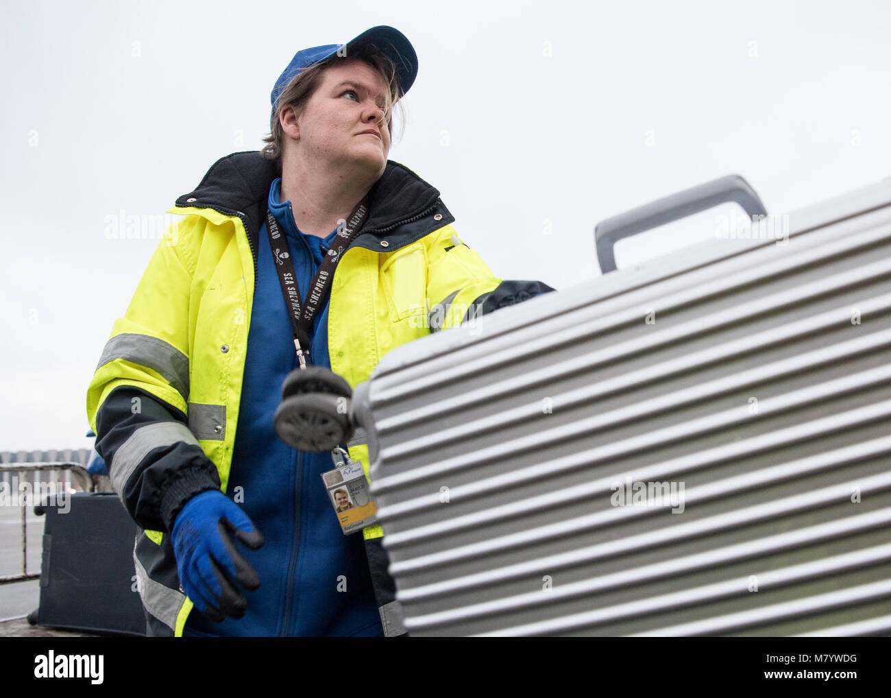 08 March 2018, Germany, Frankfurt: Sabrina Boock, in charge of ground handling operations, loads a suitcase into Stock Photo