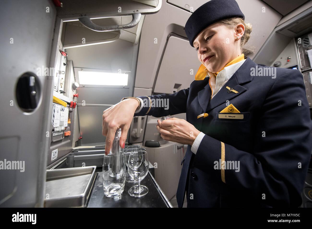08 March 2018, Germany, Frankfurt: Lufthansa flight attendant Mrs Meyer prepares glasses with drinks for boarding - Stock Image