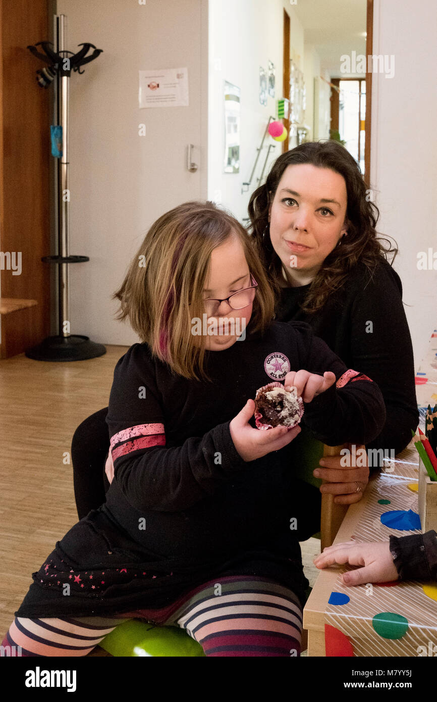 08 February 2018, Germany, Oranienburg: Nora (front), a child with Down's syndrome, eats a chocolate muffin - Stock Image