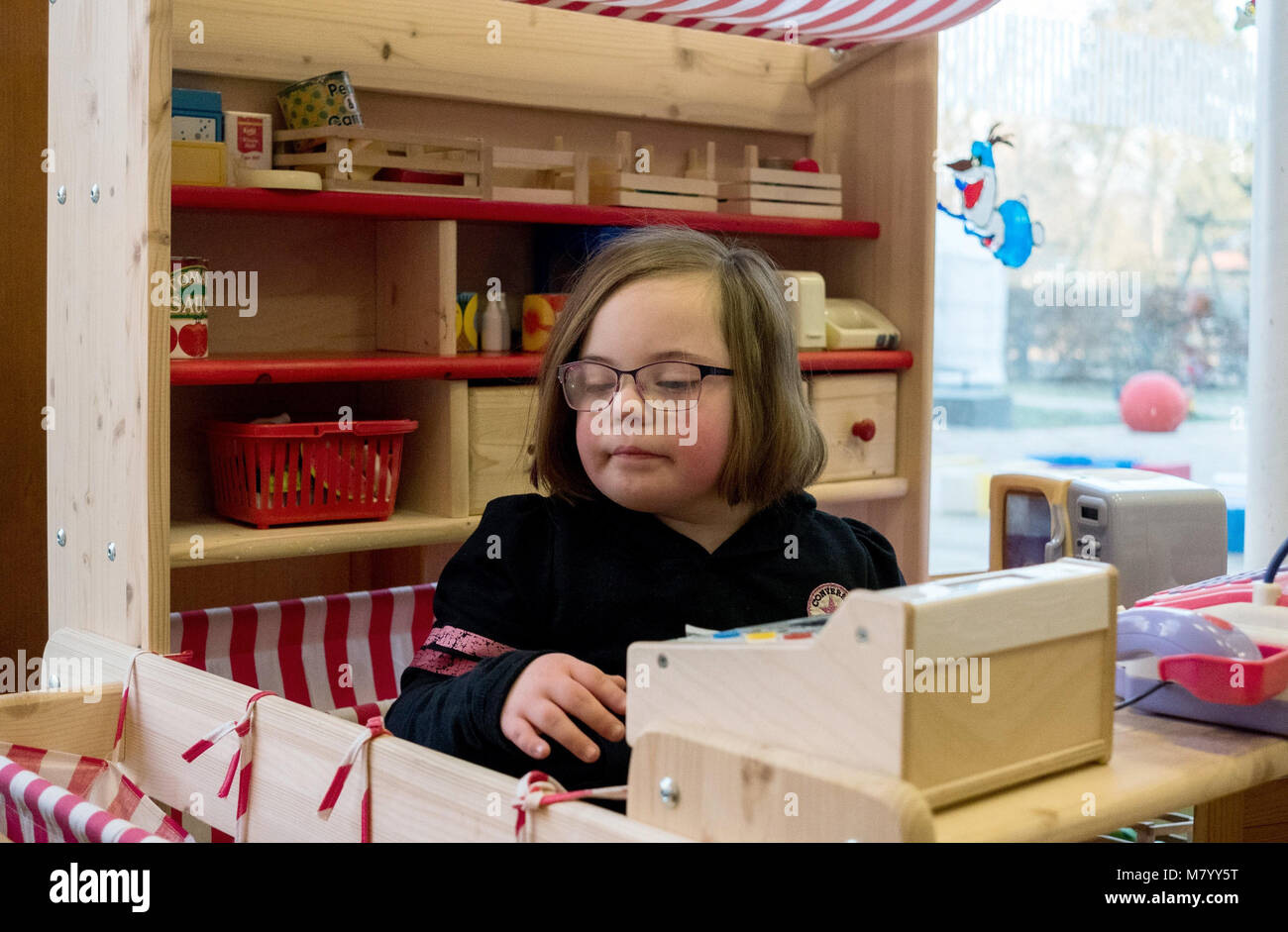 08 February 2018, Germany, Oranienburg: Nora, a child with Down's syndrome, plays with a till at the parent - Stock Image