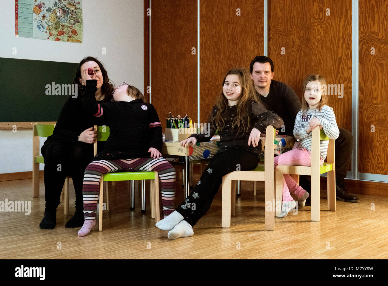 08 February 2018, Germany, Oranienburg: Nora (2nd L), a child with Down's syndrome, sits between her parents - Stock Image