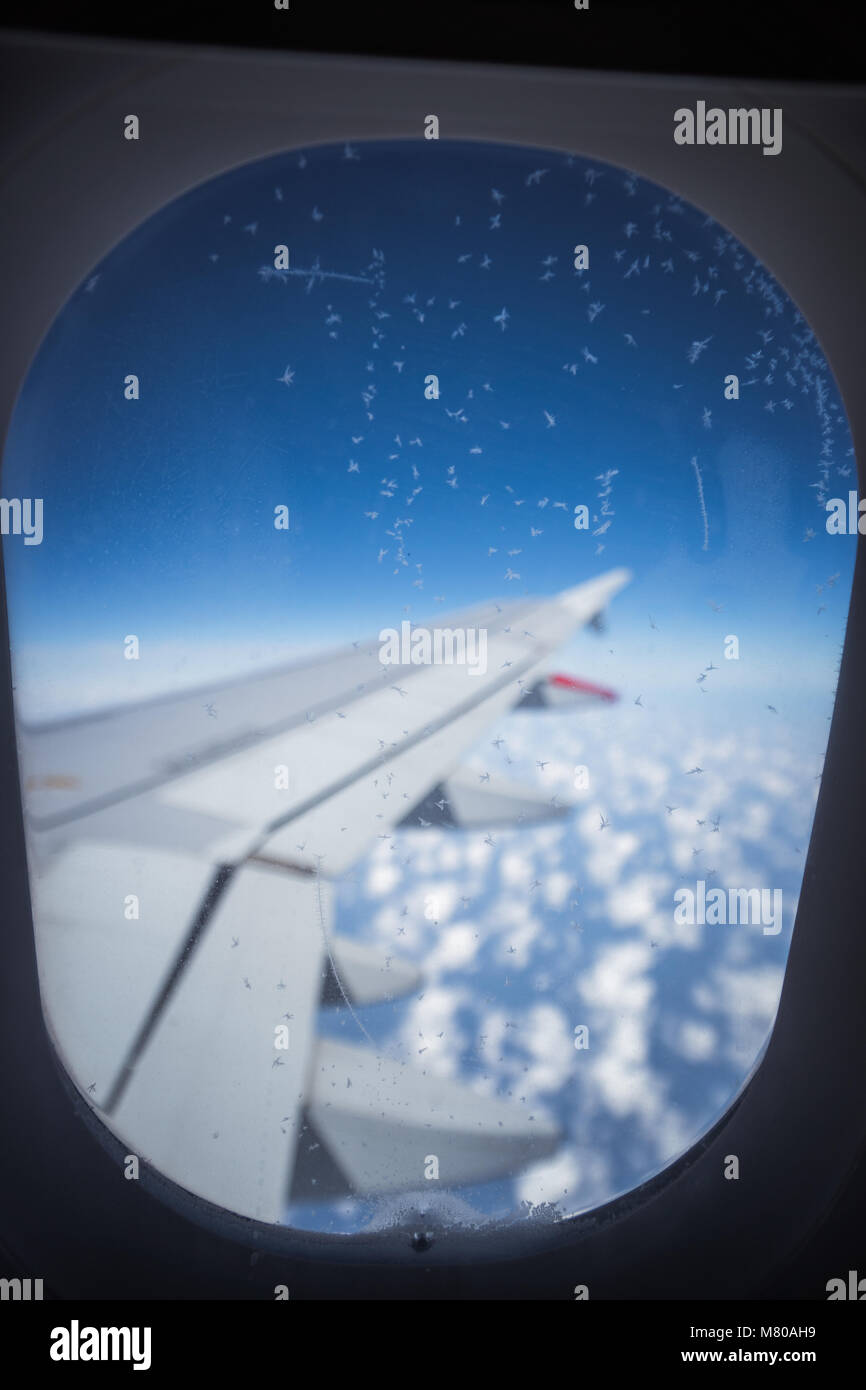 Clouds and sky as seen through window of an aircraft. Small ice crystals on the window Stock Photo