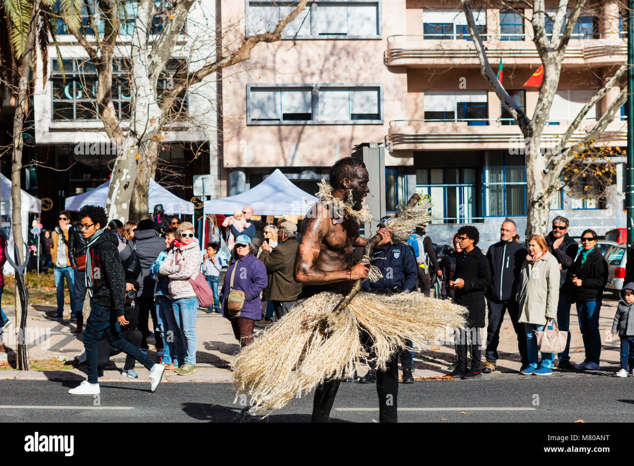 African dancer in costume at a procession on the Av. da Liberdade in Lisbon. - Stock Image