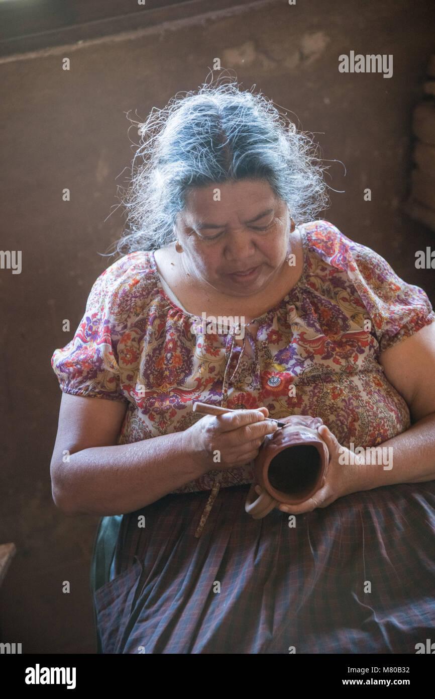Ceramic artist Maria Fabian carves traditional Purepecha designs into a cup at their home in Santa Fe de la Laguna, - Stock Image