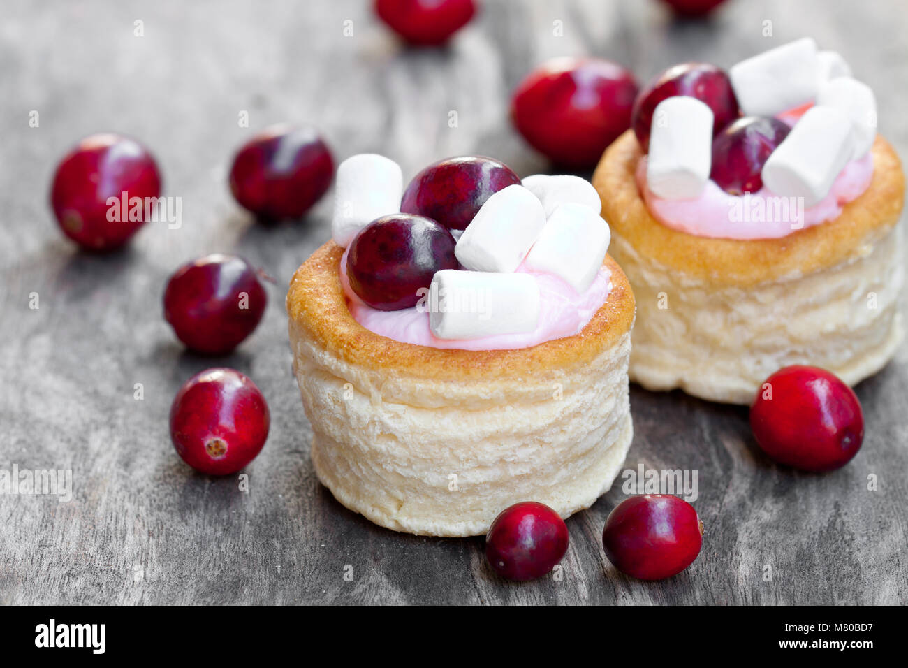 puff  pastry stuffed with fruity soft cream cheese and cranberry on wooden background - Stock Image