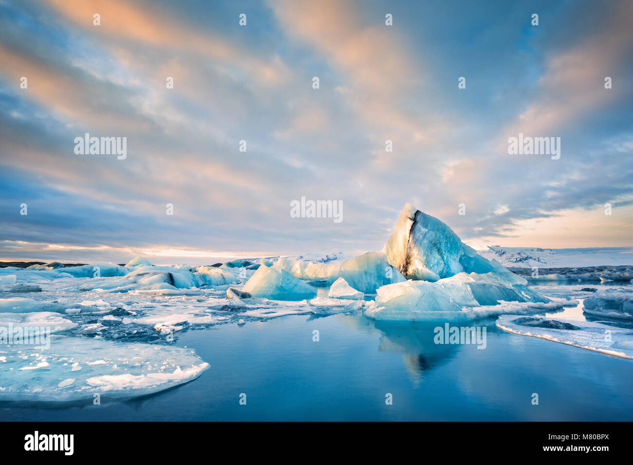 Icebergs float on Jokulsarlon glacier lagoon at sunrise, in Iceland. - Stock Image