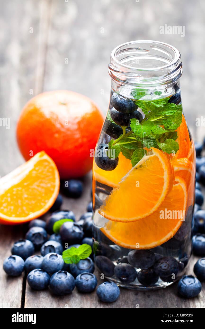 detox  organic blueberry and orange drink on wooden background - Stock Image