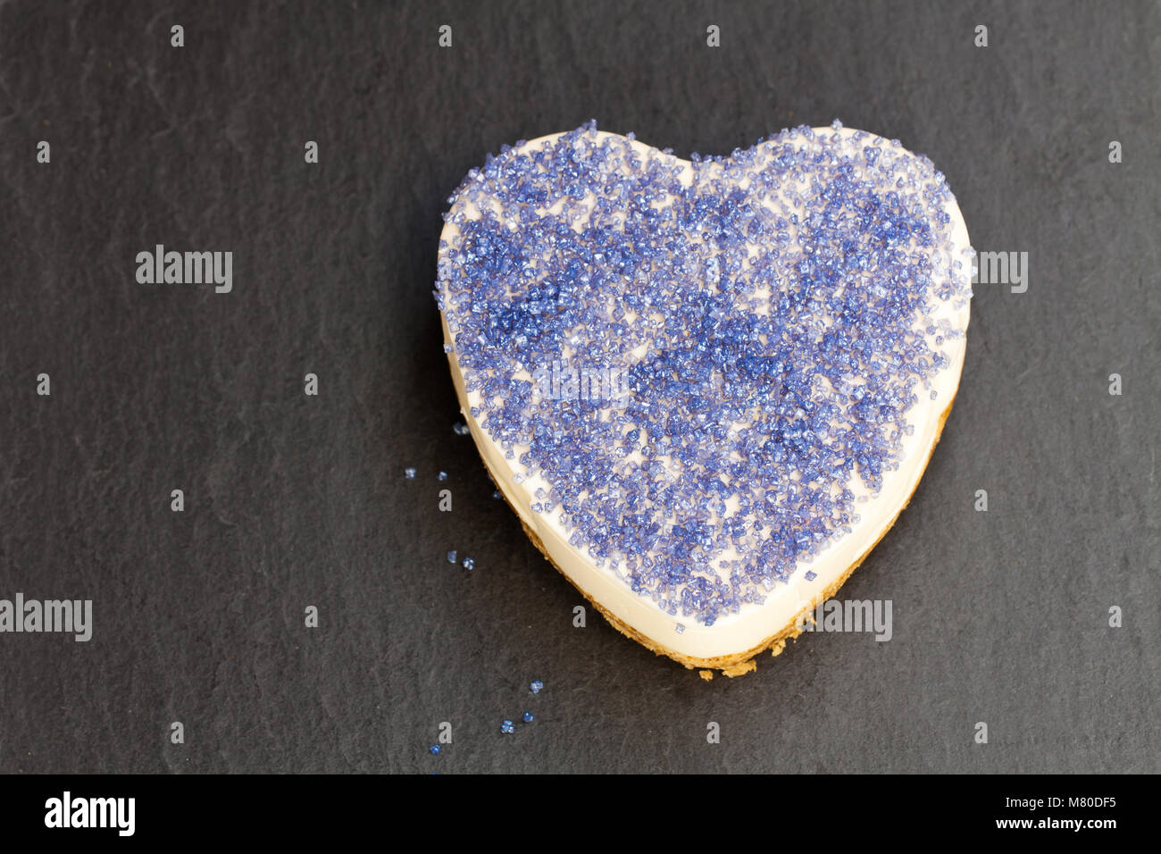 Valentines  day dessert. Heart shaped cheesecake with blue glimmer sugar. - Stock Image