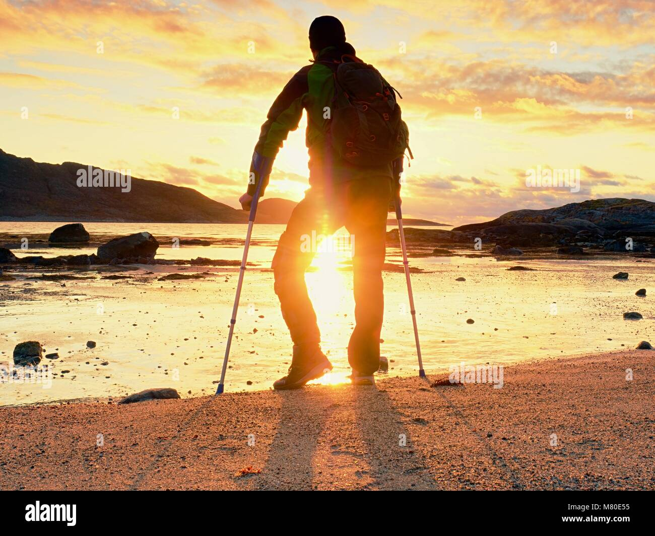 Disabled hurt hiker man is  celebrate alone attachment of his target. Tourist  stand or walk along sea water - Stock Image