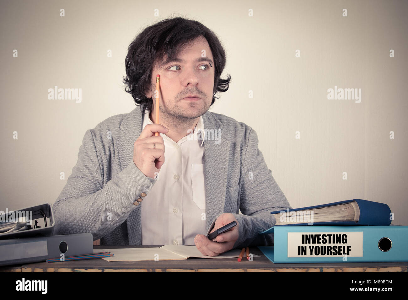 Investing In Yourself on the binder, worried bussinesman thinking by the work desk - Stock Image