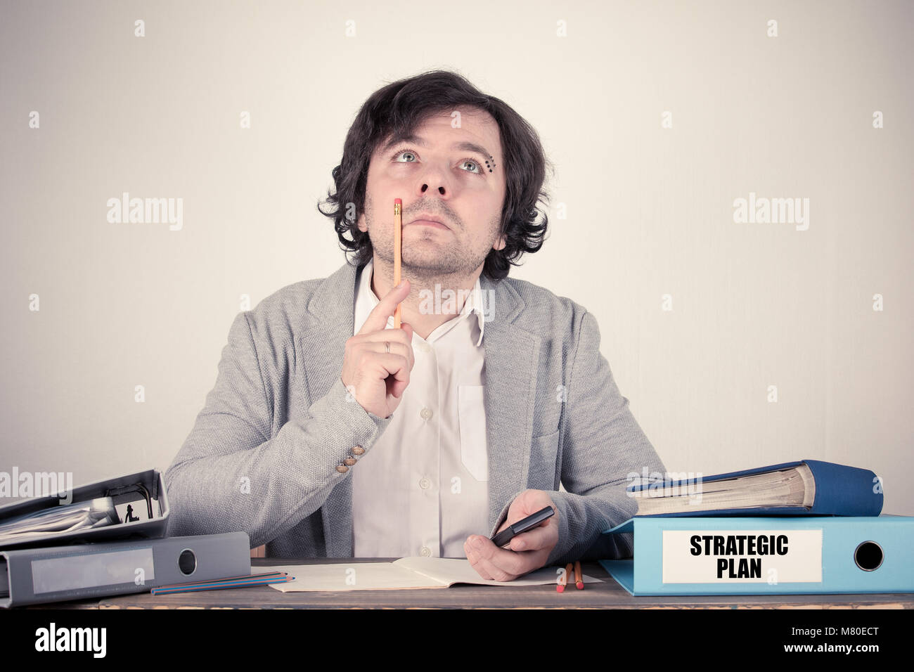 Strategic Plan text on the binder, worried bussinesman thinking by the work desk - Stock Image