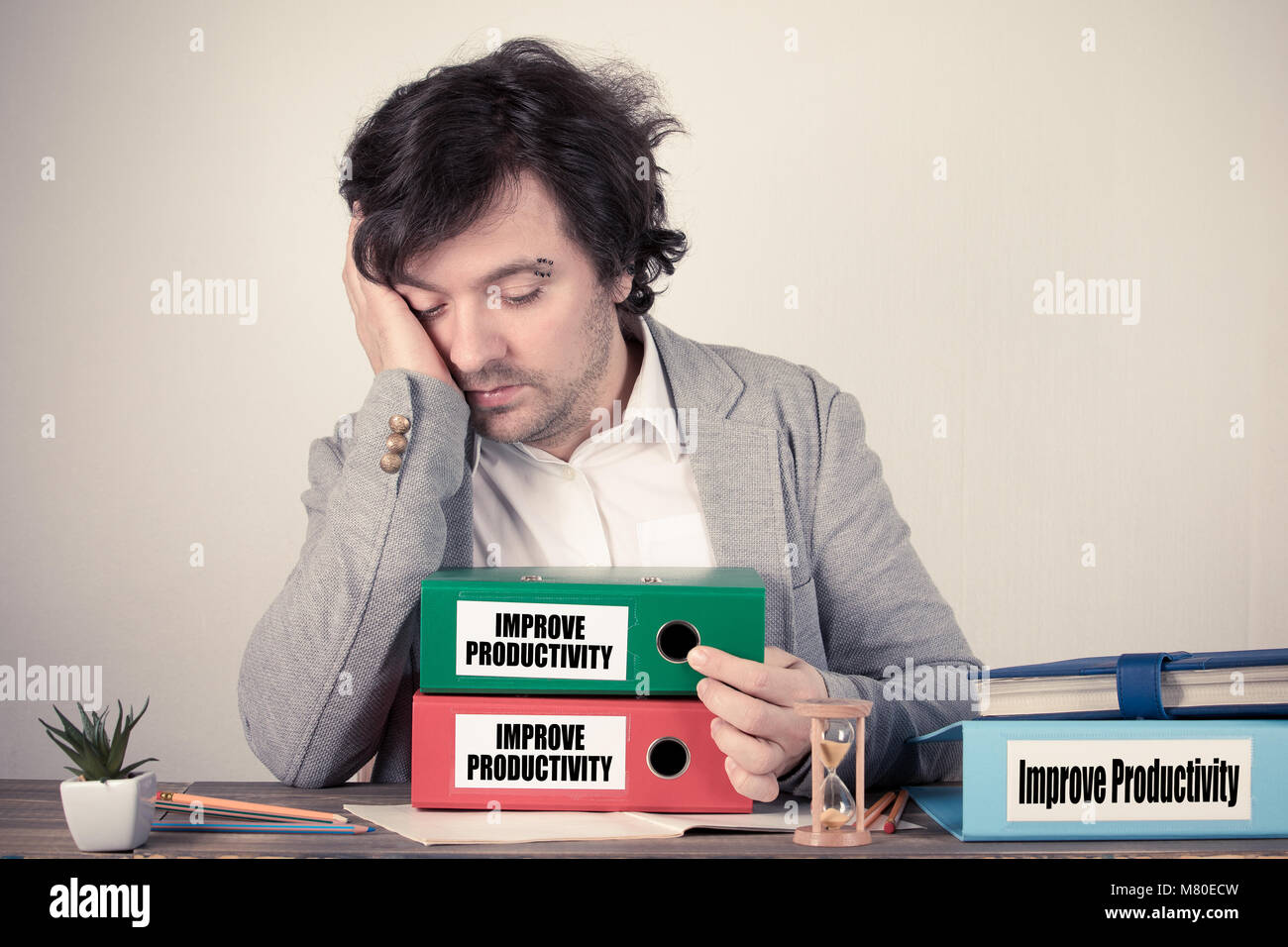Improve Productivity text on the binders, worried bussinesman thinking by the work desk - Stock Image