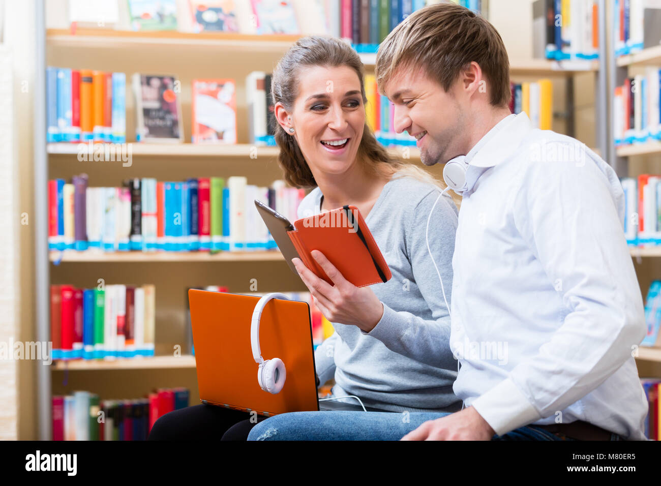Woman and man reading e-book in library - Stock Image