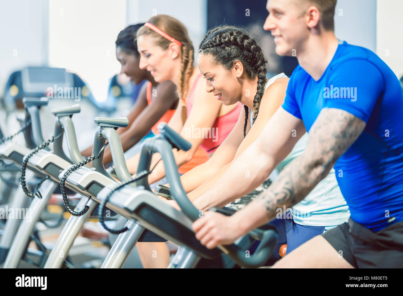 Side view of a beautiful woman smiling while cycling during spinning class - Stock Image