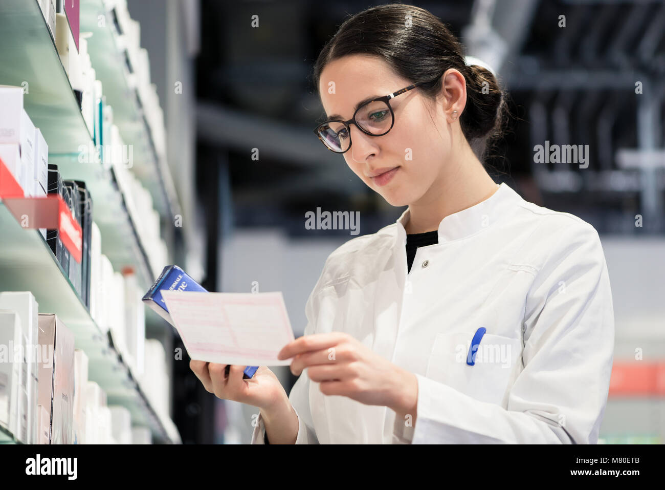 Low-angle portrait of female pharmacist checking a medical prescribtion - Stock Image
