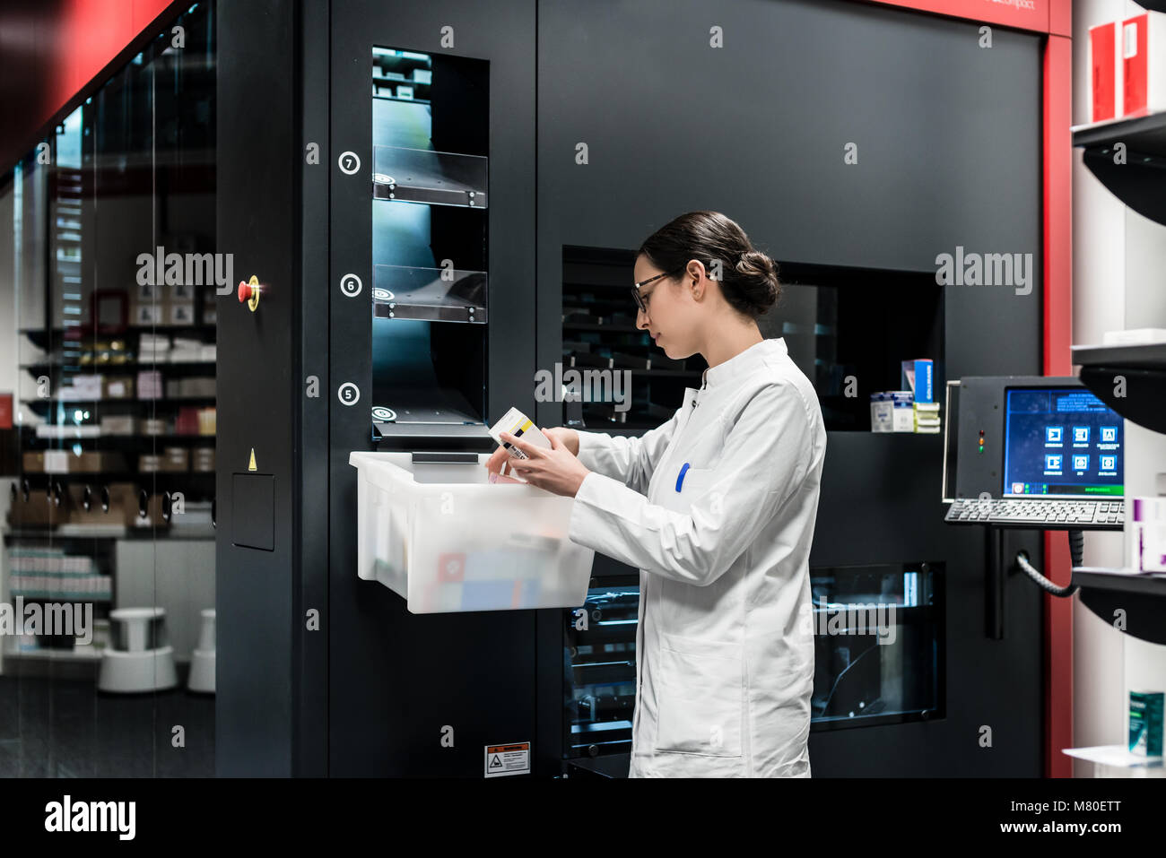 Pharmacist using a computer while managing the drug stock - Stock Image