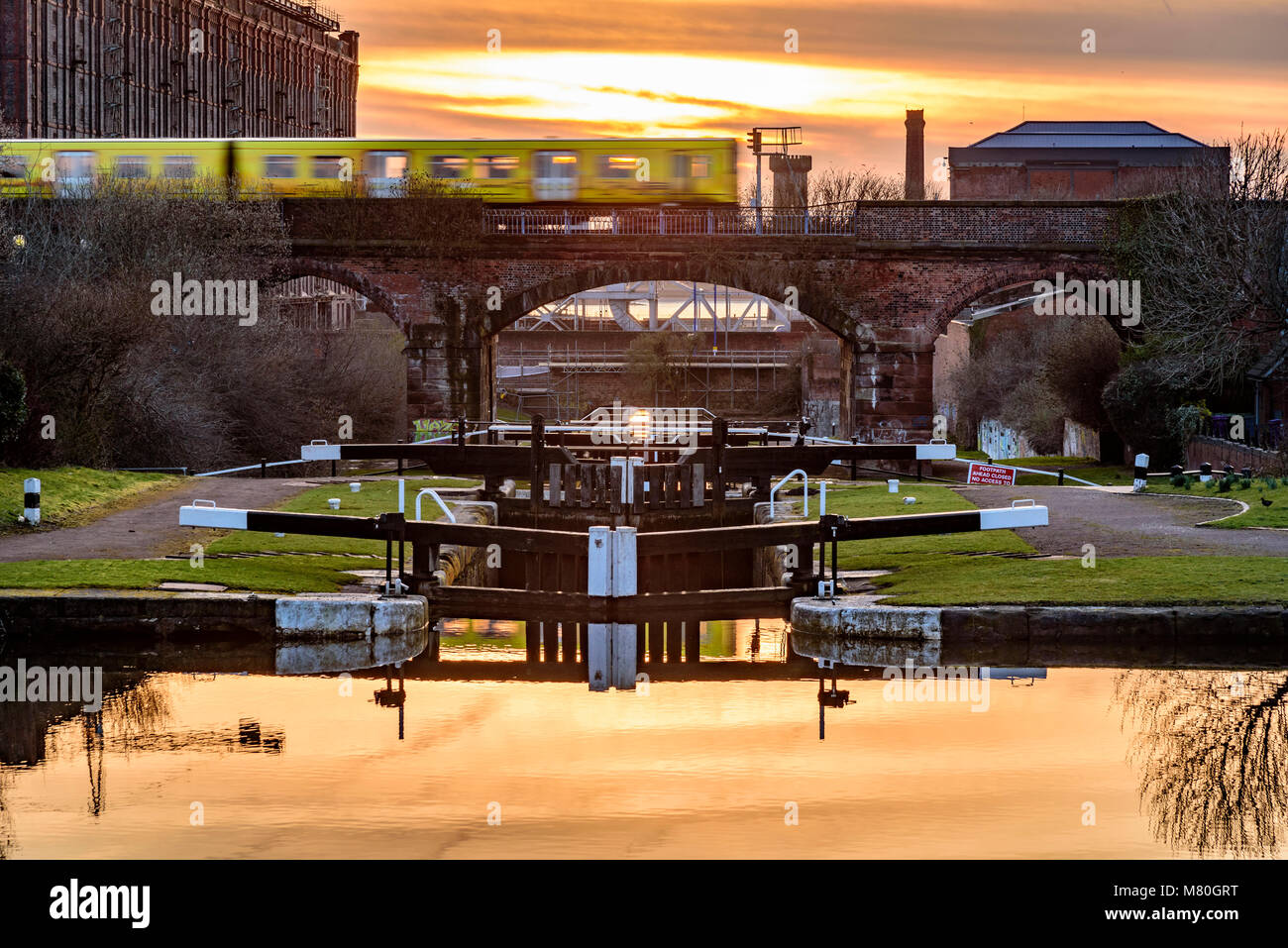 Merseyrail Electric train passing over the Leeds Liverpool canal locks at Stanley Dock. Evening light. Sunset Stock Photo