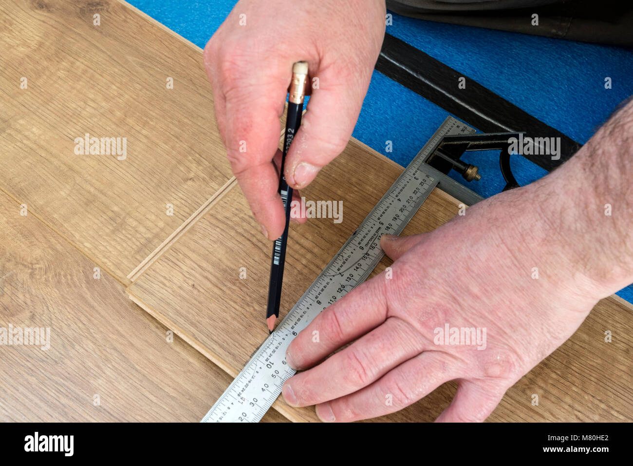 A Person Marking Out a Laminated Floor Board Ready for Cutting Using a Combination Set Square, UK. - Stock Image
