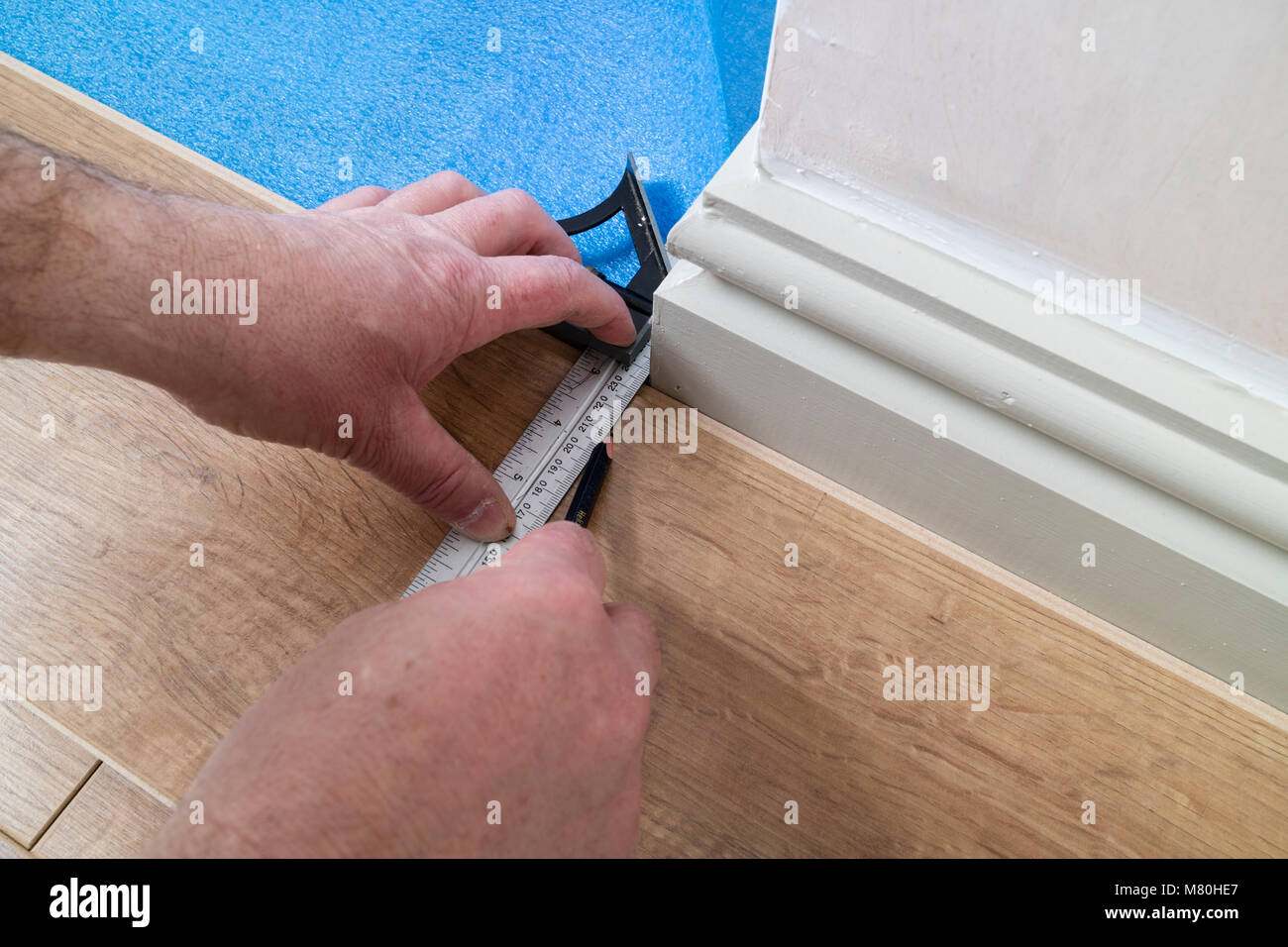 A Person Marking Out a Laminated Floor Board Using a Combination Set Square to Mark Out a Corner, UK. - Stock Image