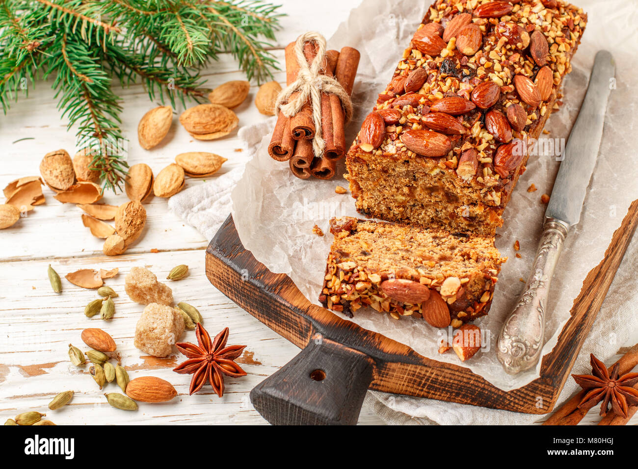 Festive Homemade Holiday Fruitcake with Nuts, Fruit and spices. Almonds, cinnamon, star anise, cardamom on the table. - Stock Image