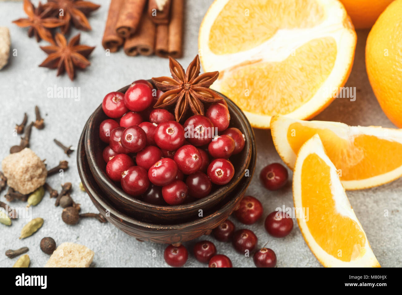 Ingredients for cooking traditional spicy winter drinks - cranberry, citrus, cinnamon, cardamom, star anise, cloves, - Stock Image
