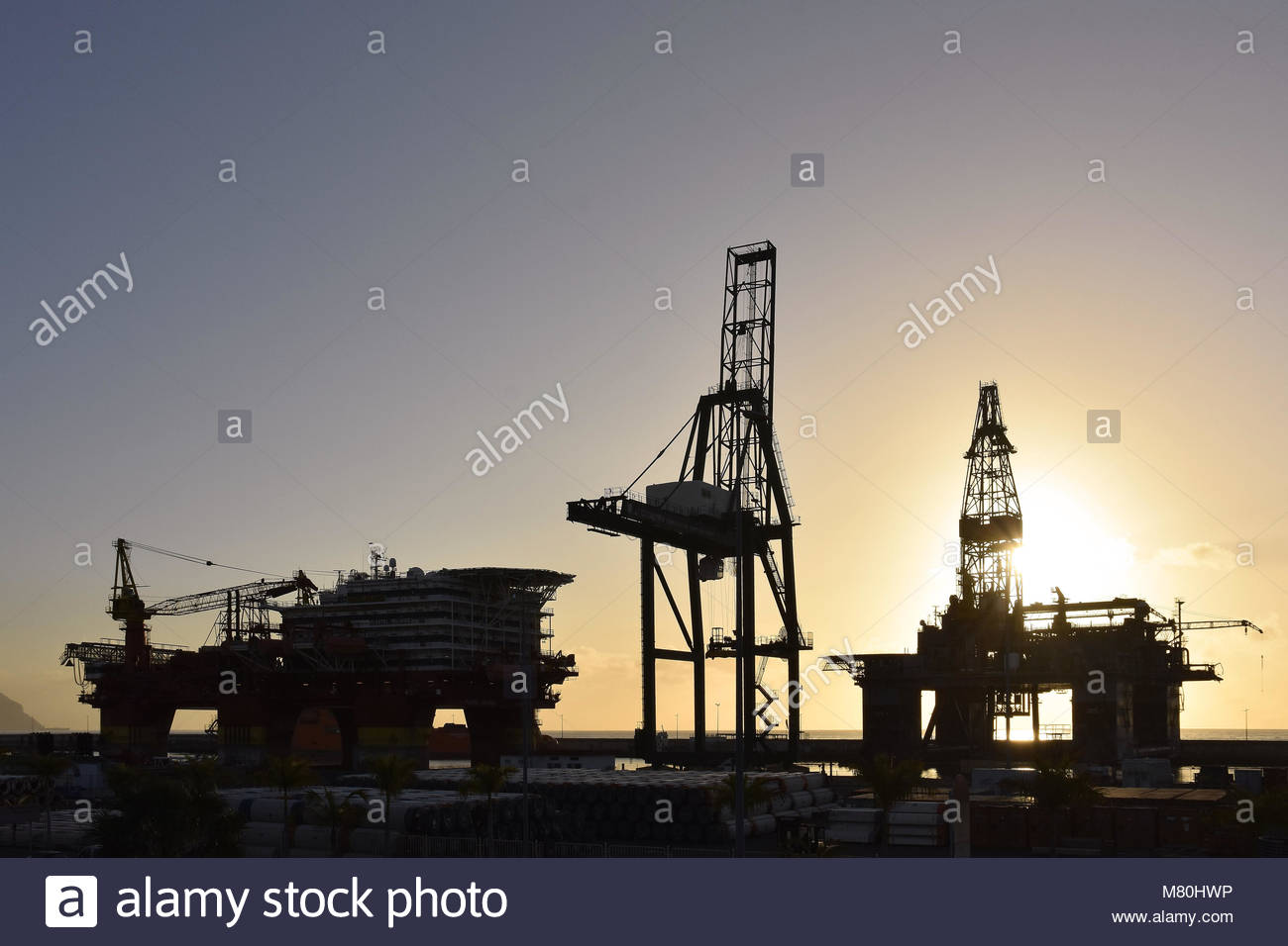 Cranes and oil rig platforms silhouetted against morning sun in the port of Santa Cruz de Tenerife Canary Islands - Stock Image